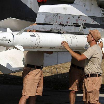 sotilaat kiinnittävät ohjusta lentokoneeseen