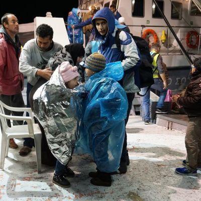 Lämpöpeittoihin kiedottuja lapsia ja muita ihmisiä aluksen kannella.
