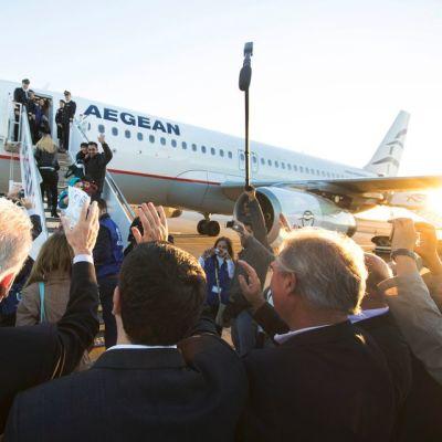 Poliitikot huiskuttavat lentokoneeseen nouseville pakolaisille.