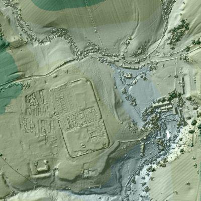 Vihertävä maastokuva, jossa näkyy koholla roomalaislaikaisten rakennusten jälkiä.