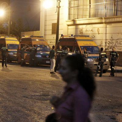 Ambulansseja jonossa Tahrir-aukion lähellä 5. heinäkuuta. Nainen kävelee kadun poikki.