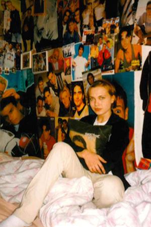 Ett foto från 90-talet där Lisa Ahlvik sitter i sin säng omgiven av affischer.