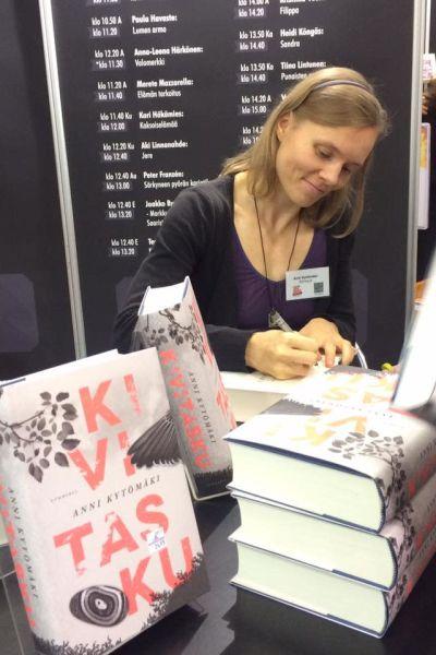 Kirjailija Anni Kytömäki istuu tyytyväisin ilmein pöydän takana kirjoittamassa omistuskirjoitusta kirjaansa. Etualalla Kivitasku-nimisiä romaaneja pinossa ja pystyssä kansi kohti kuvaa. Kannessa kuva lehtipuun oksasta ja linnun siiven kärjestä.
