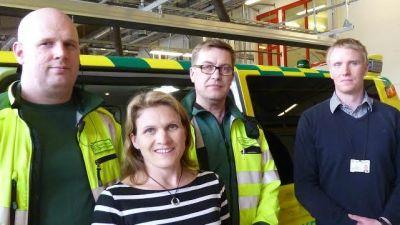 Tre män och en kvinna står och ler framför en ambulans inne på en brandstation.