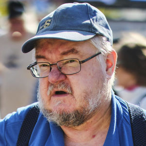 Pekka Kataja talar med en person som har ryggen mot kameran. Kataja har en blå pike-skjorta med Sannfinländarnas partilogo på sig.