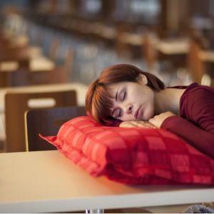 Nainen nukkuu tyhjässä kahvilassa