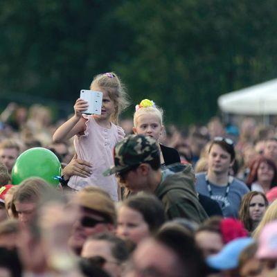Nuorinta yleisöä istuu vanhempien katselijoiden olkapäillä.