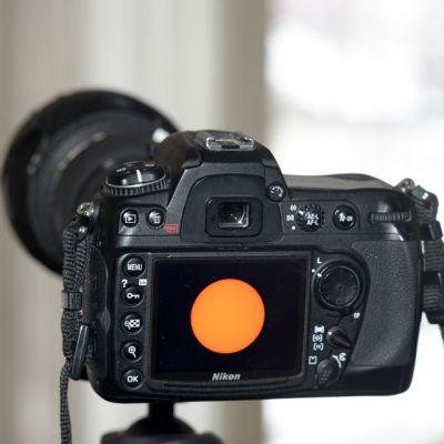 Auringon kuvaamiseen tarkoitetun suotimen läpi aurinko näkyy appelsiinin värisenä pallona.