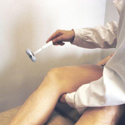 Lääkäri testaa potilaan refleksejä.