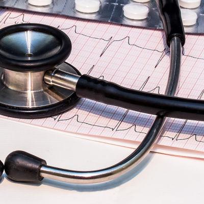 Logo för Pihlajalinna och ett stetoskop och piller på en bild av hjärtfilm