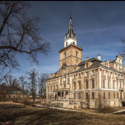 Ruskea palatsi, jonka keskiosassa on valkohuippuinen torni.