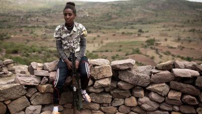 Teheras Tsega Berhan sitter på en stenmur med ett vapen i handen,