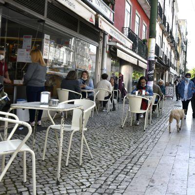 Folk sitter vid en uteservering i Lissabon.