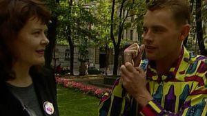 Elokuvaohjaaja Stephan Elliott ja toimittaja Kati Sinisalo keskustelevat Helsingin Ruttopuistossa syyskuussa 1994. Kuvakaappaus tv-ohjelmasta Noitaympyrät..