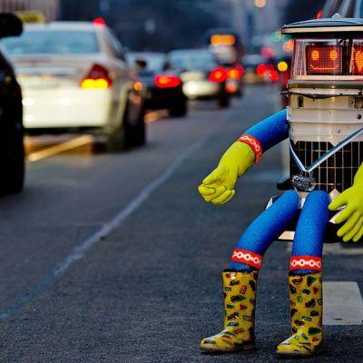 Liftaava robotti hitchBOT istuu tienvarressa.