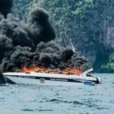 brinnande liten motorbåt framför grönskande ö