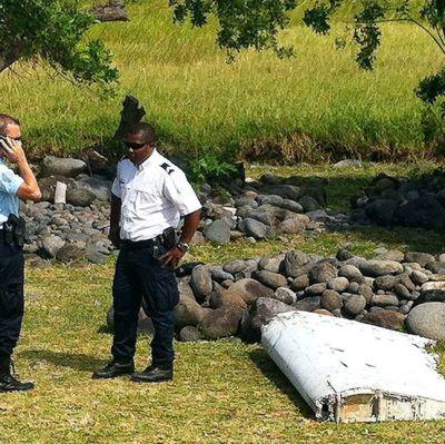 Poliser bredvid de upphittade vrakdelarna på den franska ön Réunion den 29 juli 2015.