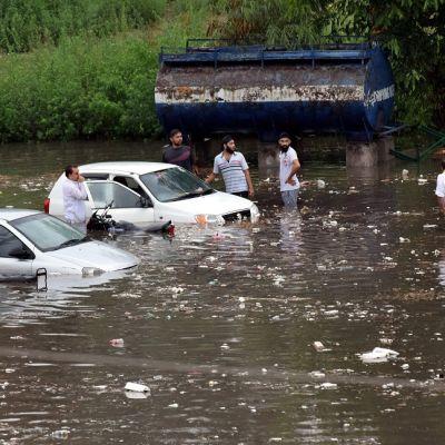 Kaksi autoa on puoliksi upoksissa tulvavesissä. Miehet kahlaavat reisiä myöten vedessä.