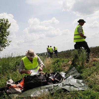 Tutkijoita MH17 lennon putoamispaikalla 19.kesäkuuta lähellä Donetskia.