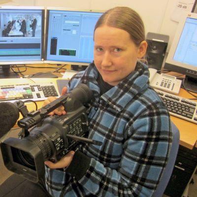 Kristiina Lehto kameran kanssa editointiyksikön äärellä