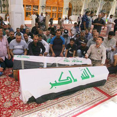 Irakilaisia rukoilemassa Bagdadin pommi-iskujen uhrien arkkujen äärellä Najafissa sunnuntaina.