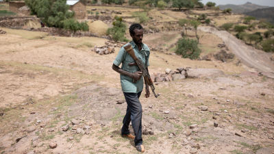 Soldaterna rör sig främst till fots i Tigrays bergiga terräng. På bilden syns en gående soldat iklädd grön skjorta och jeans samt ett vapen över bröstet.