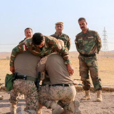 Finländare utbildar peshmergasoldater i Irak i november 2019. Soldaterna står i en halvcirkel och tittar på två soldater som lyfter upp en annan soldat.