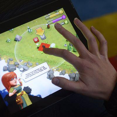 Pelaaja pelaamassa Supercellin suunnittelemaa Clash of Clans -peliä iPadillä.