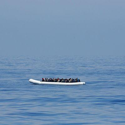 Ihmisiä täynnä oleva suuri kumivene aavalla merellä.