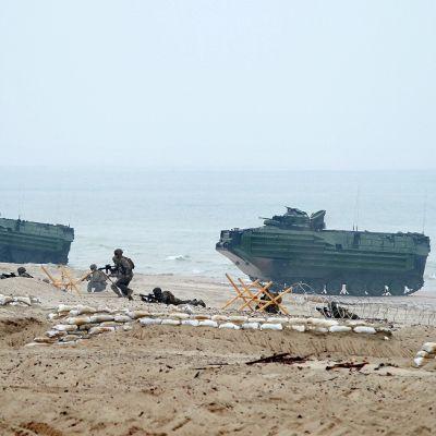 Kaksi maihinnousuajoneuvoa ja joukko sotilaita etenee merenrannalla.