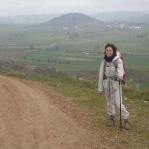 Santiago de Compostelan pyhiinvaellusreitillä tien reunassa avarassa maisemassa taustalla matalaa vuoristoa, Manuela Bosco seisoo vaellussauvaan nojaten ja katsoo kameraan.