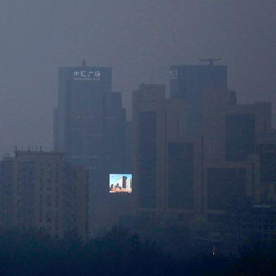 Suuressa LCD-näytössä loistaa sininen taivas savusumun peittämän pilvenpiirtäjän seinässä