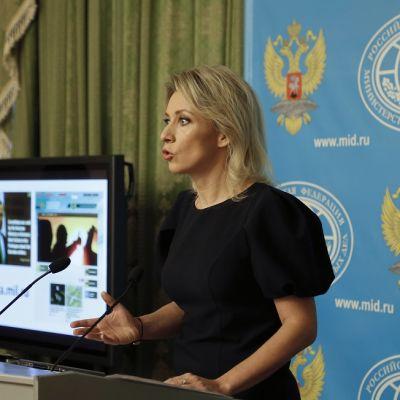Musta-asuinen Zaharova puhuu puhujanpöntön takana. Taustalla näkyy Venäjän ulkoministeriön logoilla ja Venäjän vaakunakuvilla varusteltu sininen kangas ja vihreää verhoa.