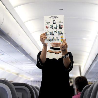 Lentoemäntä esittelee turvaohjetta.