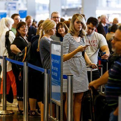 Ihmiset jonottivat lentoasemalla.