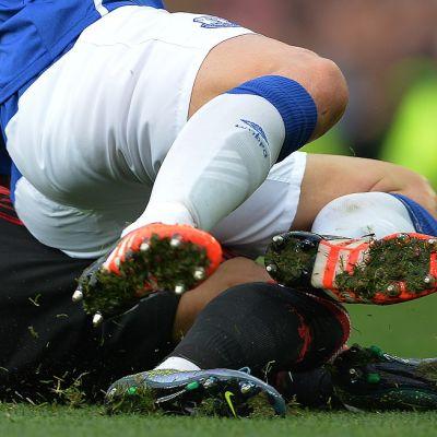 Kaksi jalkapalloilijaa taklaustilanteessa.