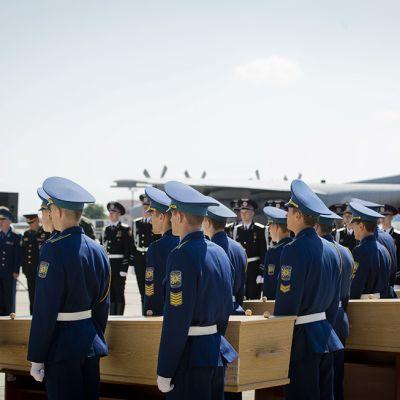 Ukrainalaissotilaat kantoivat arkkuja lentokoneeseen Kharkivin lentokentällä 23. heinäkuuta.