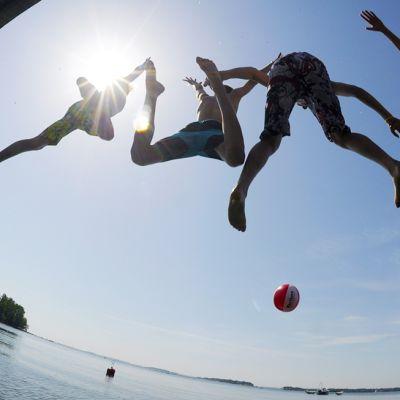 Neljä poikaa hyppäämässä veteen.