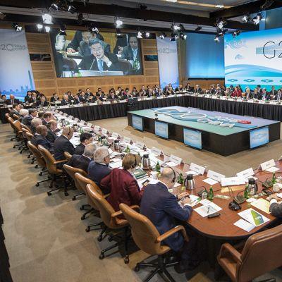kymmeniä ihmisiä salissa istuu kokouspöydissä