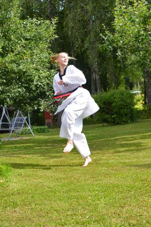En ung kvinna i taekwondodräkt står ute på en gräsmatta. Hon håller på med att påbörja ett hopp.