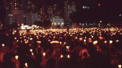 Personer står i en park och håller upp ljus.