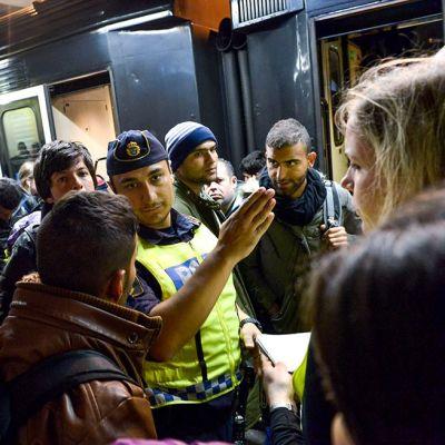 Poliisi opasti siirtolaisia Tukholman juna-asemalla 12. syyskuuta.