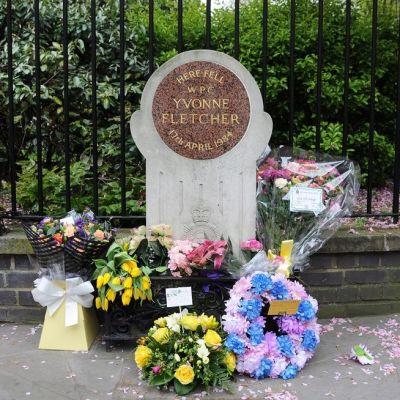 """Puiston aidan vieressä on valkoinen muistokivi, jonka laatassa lukee englanniksi: """"Tässä kaatui naiskonstaapeli Yvonne Fletcher huhtikuun 17. päivänä 1984. Muistomerkin edessä on kukkakimppuja."""