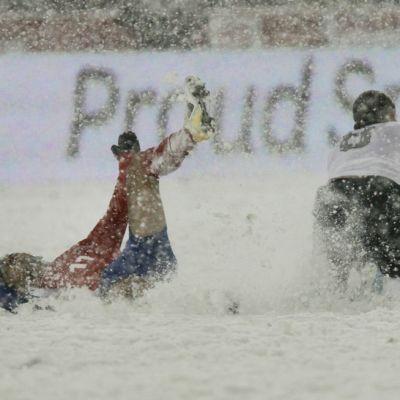 Costa Rican Michael Barrantes (vas.) kaatuu lumen peittämällä kentällä. Vieressä nurin myös Yhdysvaltain Clint Dempsey (oik.).