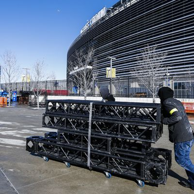 Kylmä säätä vastaan pukeutuneet työntekijät työntävät metallitelineitä kohti MetLife -stadionia New Jersey:ssä 29. tammikuuta.