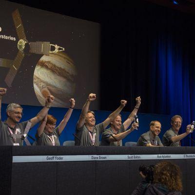 Joukko Juno-työryhmän jäseniä pitää käsiään voitonriemuisesti ylhäällä tiedotustilaisuudessa pöydän takana. Kaikilla on harmaat T-paidat. Taustalla on kuvaesitys luotaimesta ja planeetasta.