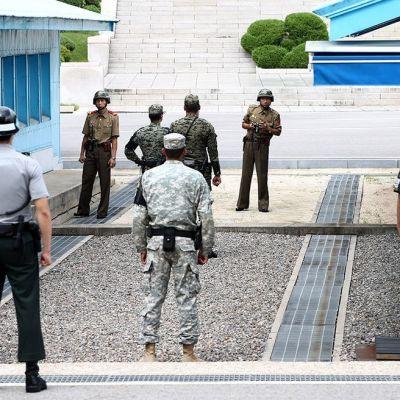 Nordkoreanska soldater (i bakgrunden) ser på sydkoreanska soldater i gränsbyn Panmunjom i juli år 2015.