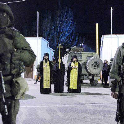 Ortodoksipapit seisovat asemiesten vartion keskellä.