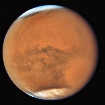 Punainen planeetta, jonka pinnalla näkyy hiekkapilviä.