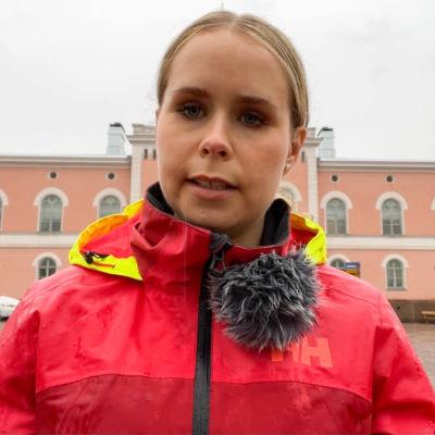 En kvinna som står framför Lovisa stadshus.